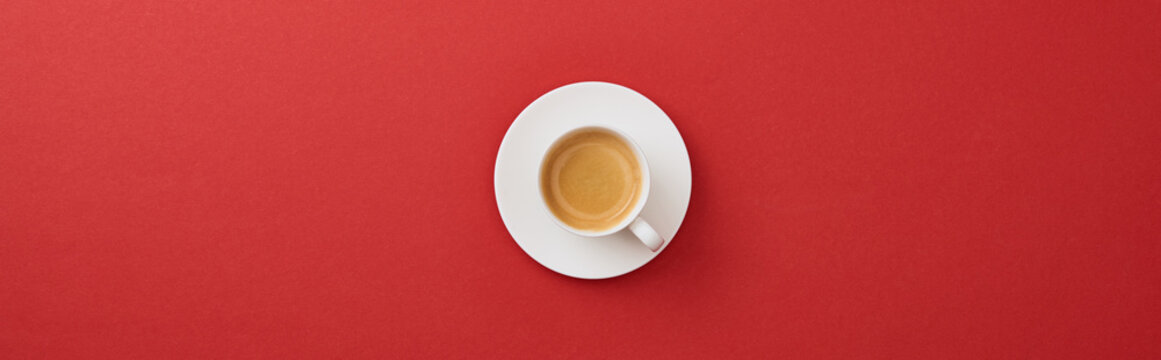 top view of white cup with fresh coffee on saucer on red background, panoramic shot