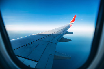 aircraft wing in the sunset light. Airplane wing against the blue sky from the porthole. view from the airplane porthole to the clouds. Fototapete