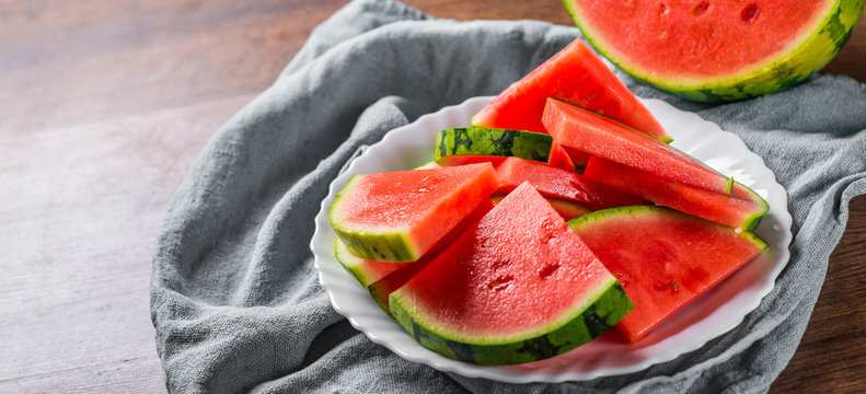 Cut slices of juicy watermelon on white plate on wooden table background