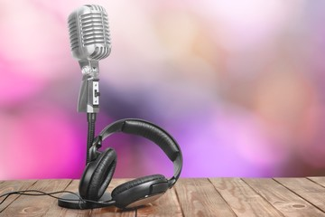 Retro style microphone and headphones on  background