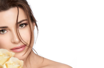 Beautiful young woman with yellow roses. Skincare and healthy cosmetology concept