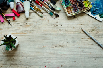 Artist paint brushes on the wooden background