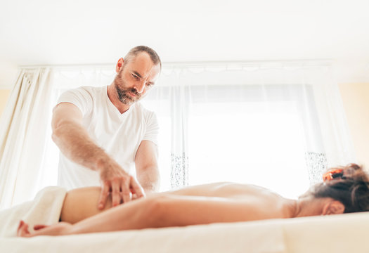 Bearded Masseur man doing massage manipulations on the lumbar area zone during young female body massage.