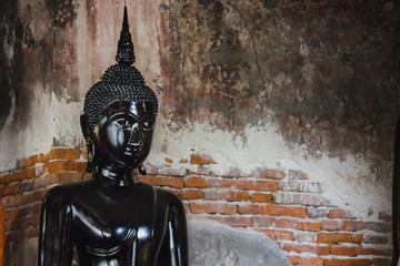 Black buddha statue with old walls in Thai temples