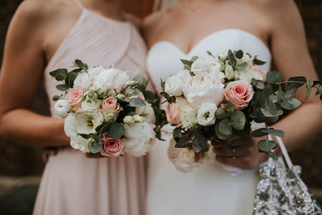 Midsection of bride and bridesmaid holding bouquet