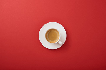 top view of white cup with coffee on saucer on red background