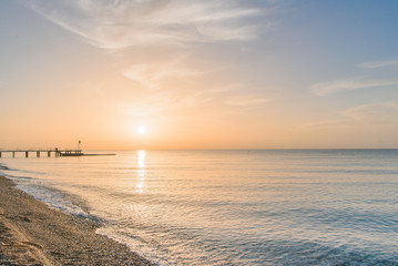 Sunrise at the sea beach. Calm sea without waves in the morning.