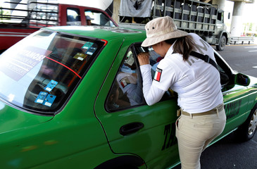 An official of the National Migration Institute checks a passenger's ID at a checkpoint on the outskirts of Tapachula