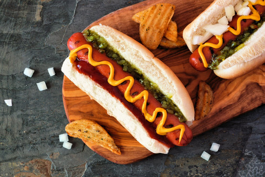 Hot dogs with toppings and potato wedges on wooden board. Close up, overhead view.