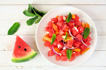 Watermelon and tomato salad with feta cheese. Top view on white plate. Table scene with a white wood background.