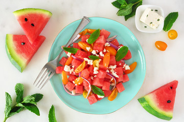 Watermelon and tomato salad with feta cheese. Overhead view on blue plate. Table scene with a marble background.