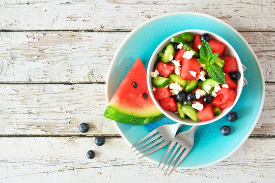Watermelon salad with cucumber, blueberries and feta cheese. Overhead view table scene on a white wood background.