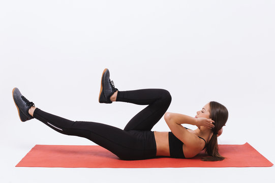 Sporty young female athlete on yoga mat doing situps over white background