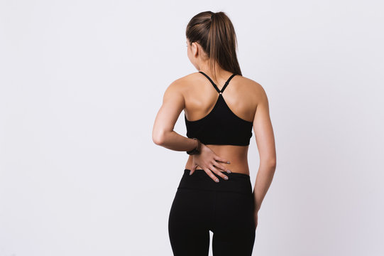 Young fitness woman feeling back pain standing over white wall