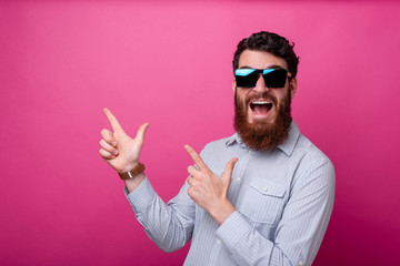 Portrait of amazed young man with beard pointing away at copyspace Wall mural