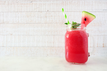 Watermelon juice in a mason jar glass. Side view against a white wood background.