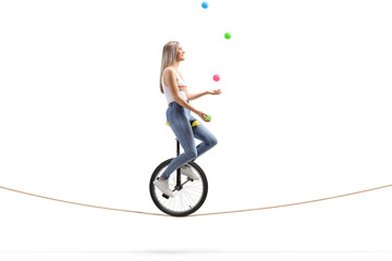 Young woman riding a unicycle on a rope and juggling with balls Wall mural