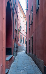 Spoed Foto op Canvas Smal steegje Street view of a narrow alley (caruggio) in the historic centre of the old town of Santa Margherita Ligure with ancient, red building exteriors and stone pavement, Genoa, Liguria, Italy