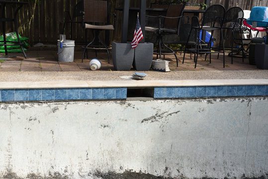 Empty swimming pool remodel with new tile and coping with American flag in background