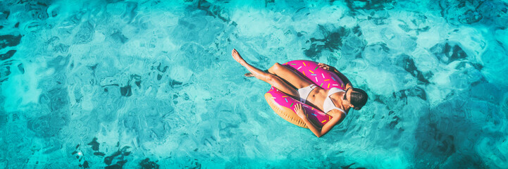 Beach vacation woman relaxing in pool float donut inflatable ring floating on turquoise ocean water background in Caribbean travel summer banner panorama. Girl in white bikini top drone view.