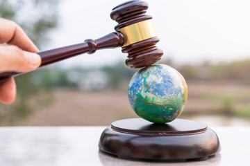 Obraz Earth destruction and destroy environmental by hand human concept. Judge gavel / world model should have legal force or certification for survival of all mankind with international Environment law - fototapety do salonu