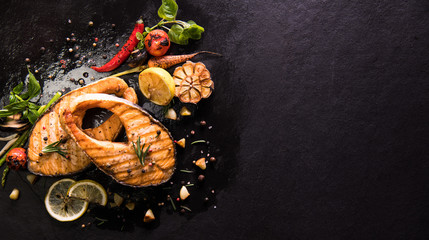 Fototapete - Grilled salmon fish with seasoning and various vegetables on black stone background