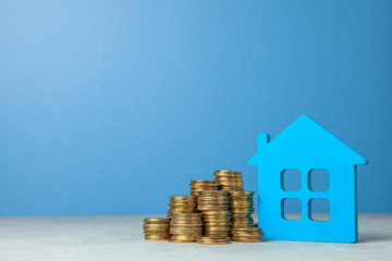 House and stack of coins. The concept of buying home or insurance. Blue background.