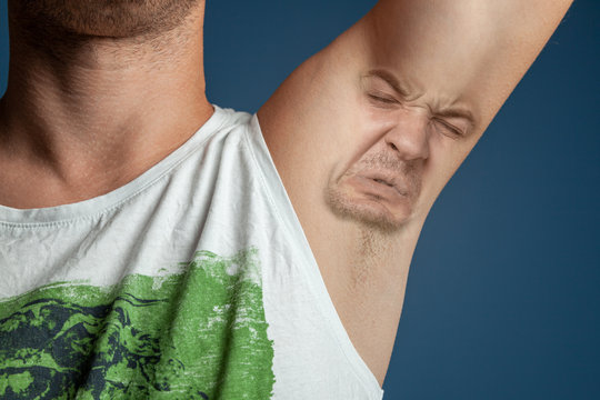 Smelly armpits in men. Concept of twisted panting face from bad smell.