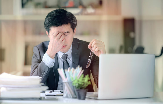 Tired frustrated businesssman feeling stressed, holding head and worried about business problem failure.