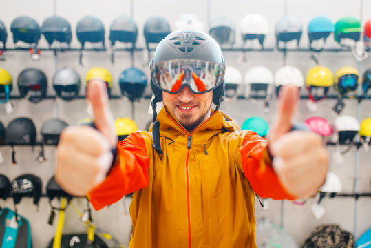 Man in helmet for snowboarding shows thumbs up