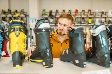 Male person choosing ski or snowboarding boots