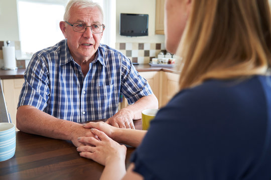 Woman Talking With Unhappy Senior Man Sitting In Kitchen At Home