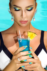 Young pretty fashion woman  posing outdoor summer on tropic island in hot weather on pool party. Beauty model with drink and amazing makeup.Portrait of sexy model in bikini at resort - Image