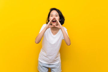 Asian young woman over isolated yellow wall shouting and announcing something Wall mural