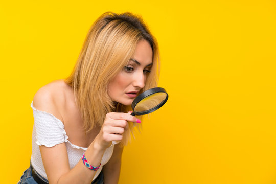 Young blonde woman over isolated yellow wall holding a magnifying glass