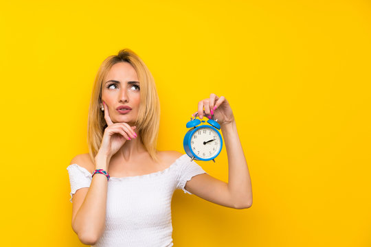 Young blonde woman over isolated yellow wall holding vintage alarm clock