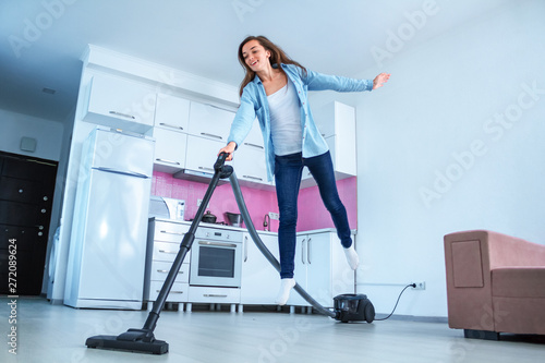 Young attractive woman vacuuming house with vacuum cleaner