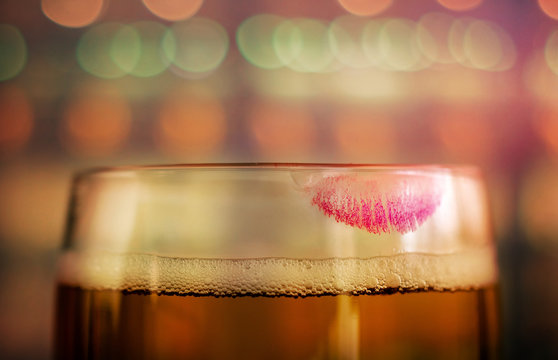 Woman Drinking Beer Concept. Closeup of Glass of Beer with Red Lipstick Mark in Bar or Restaurant. Feminine Mood