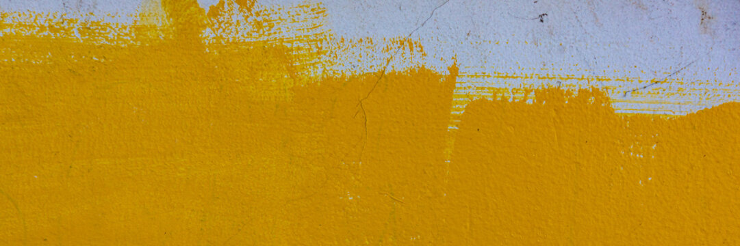 cement plaster covered with yellow paint, the surface of the wall.