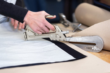 Dressmaker designer stapling fabric pattern at garment industry .