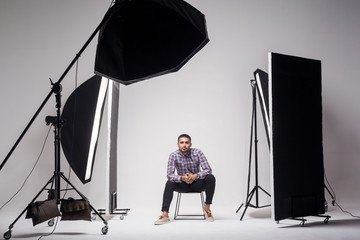 Professional photography studio showing behind the scenes lights. fashion handsome young man model at studio in the light flashes, sitting and looking at camera. indoor studio shot on grey background