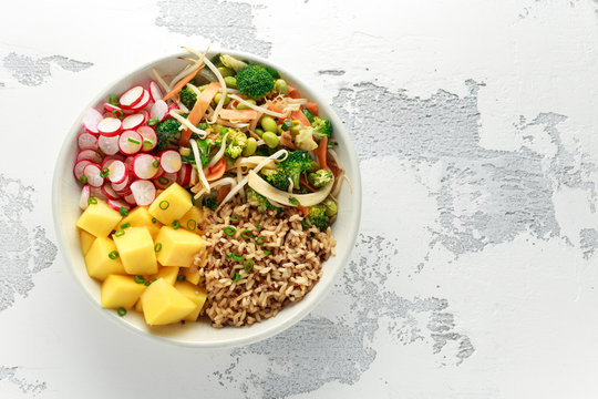 Asian style Vegan salad bowl with edamame, vegetable stir-fry mix, wholegrain rice, quinoa, mango chunks drizzled with mango, chilli dressing