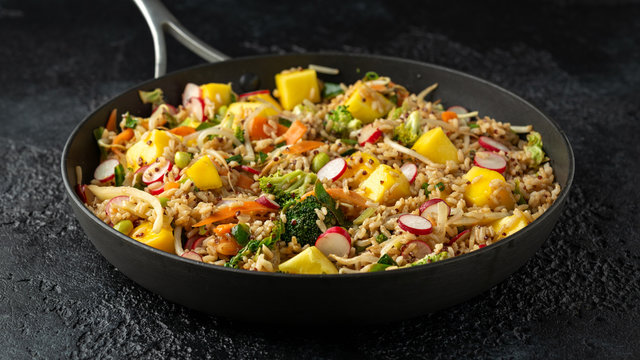 Asian style Vegan dish in pan with edamame, vegetable stir-fry mix, wholegrain rice, quinoa, mango chunks drizzled with mango, chilli dressing
