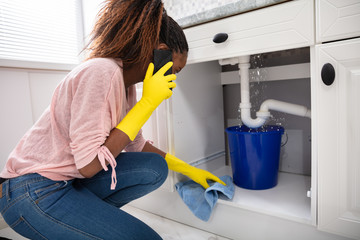 Woman Placing Bucket Under The Sink Pipe