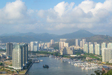 View of one of the districts of Sanya city. Visible are the skyscrapers and the public ferry terminal. Hainan Island, China.