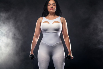 Size plus woman sporty fit woman in white sportswear, athlete with dumbbells makes fitness exercising on black background with lights. Motivation for fat people.