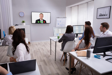 Businesspeople Attending Videoconference Meeting In Office