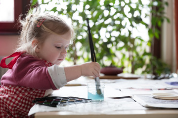 Girl painting by table at home