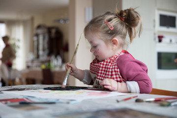 Little girl painting artwork in domestic setting at home
