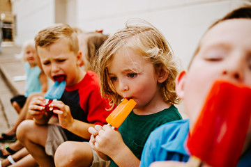 Group of Kids Eating Frozen Colorful Popsicles in the Summer